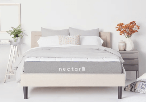 A Nectar mattress lays against a pale bedroom.