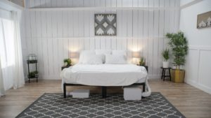 A white bedroom with a white bed and two BedJets.