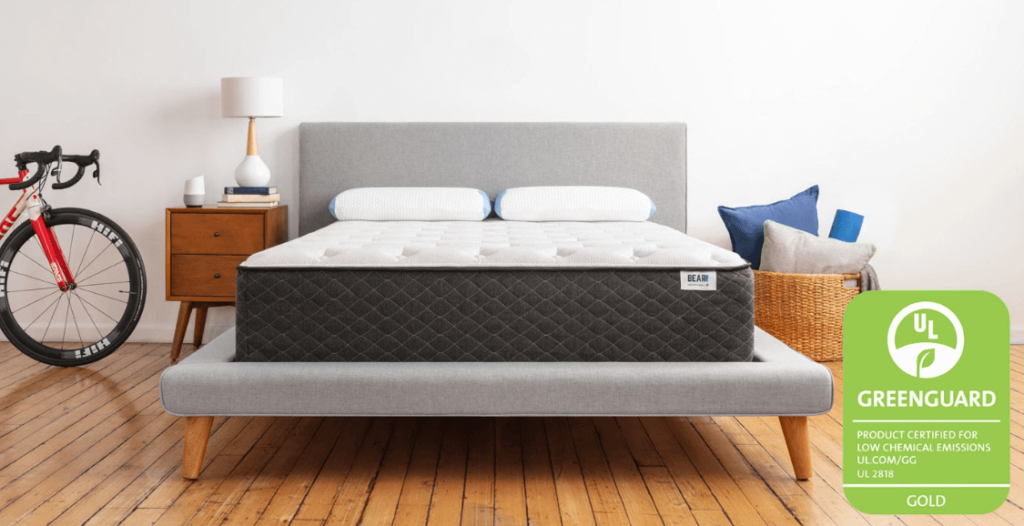 A gray and white Bear hybrid mattress on a gray bed frame.