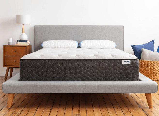 A white mattress with two white bed pillows sitting on a gray bed frame.