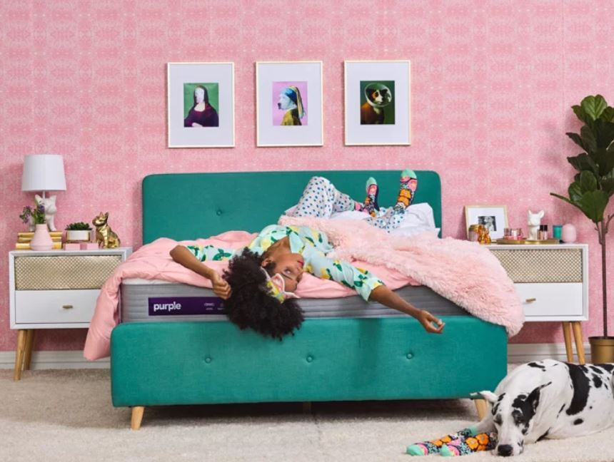 Woman laying on turquoise bed with a purple mattress.