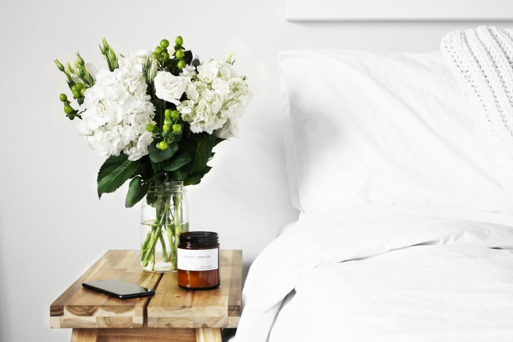 A bed with a night stand and flowers.