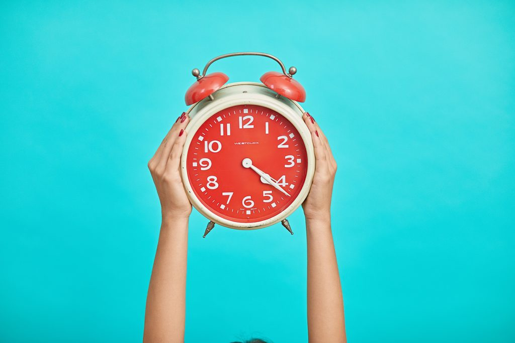 Hands holding an alarm clock against a turquoise wall.