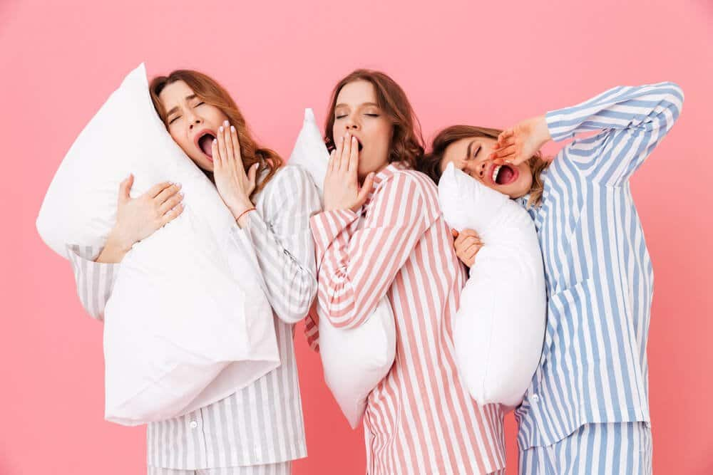 Portrait of sleeping women 20s in homewear having fun while resting at home together and yawning due to insomnia isolated over pink background.