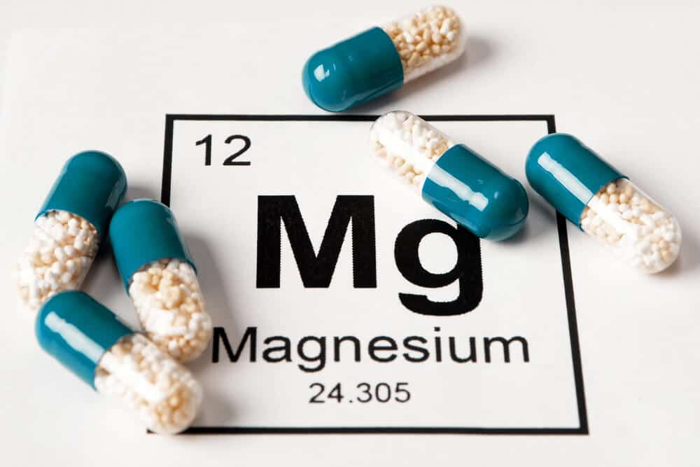 Pills with mineral Mg (magnesium) on a white background with an inscription from the chemical table.