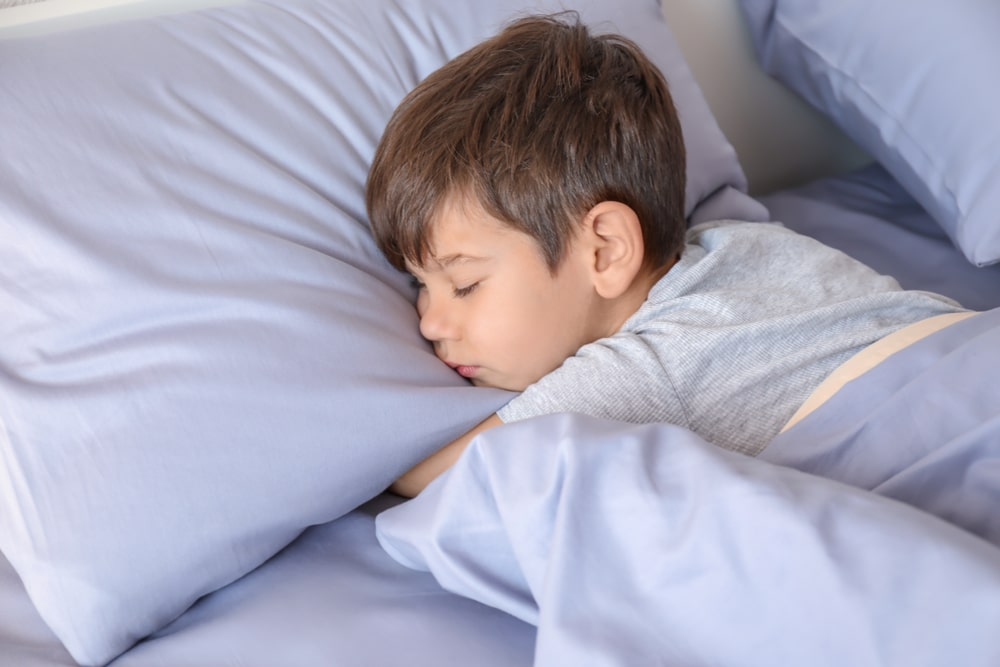 boy sleeping on a light blue pillow.