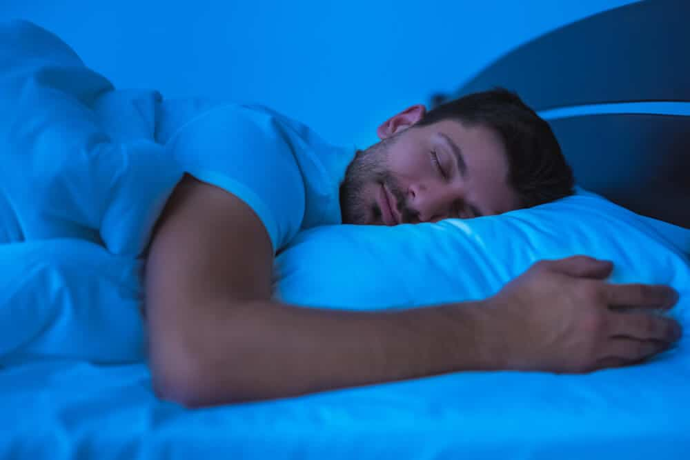 A man sleeps on a bed with white covers; concept of using the Dodow sleep aid to fall asleep.