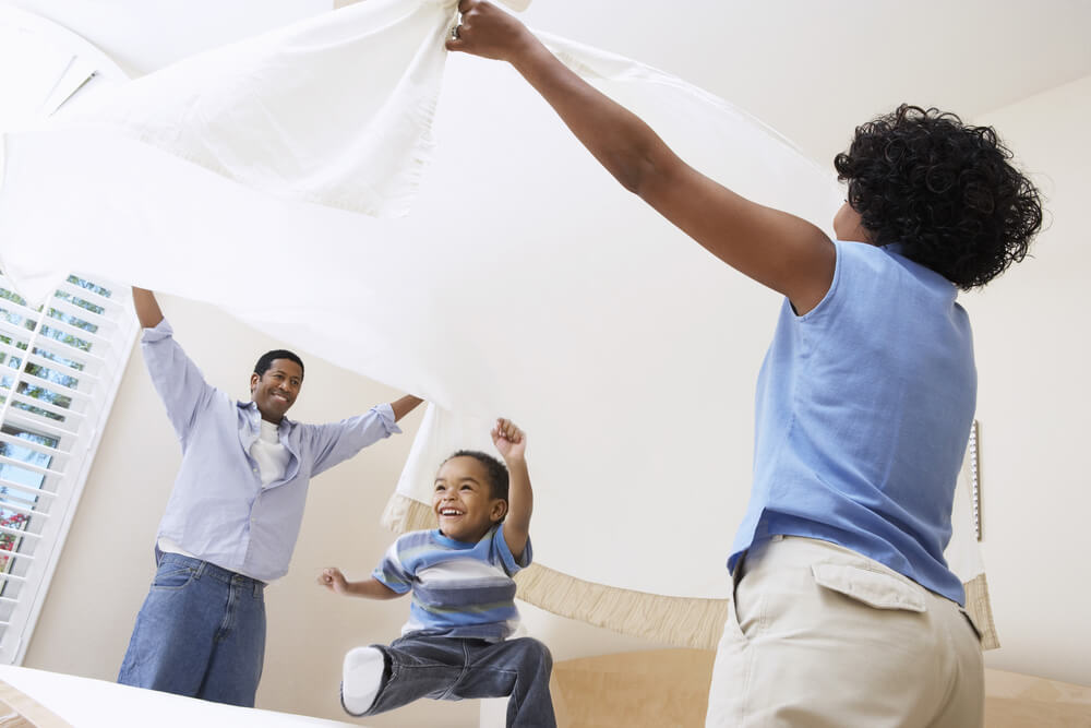 African American parents spreading softened bed sheet over son in bedroom