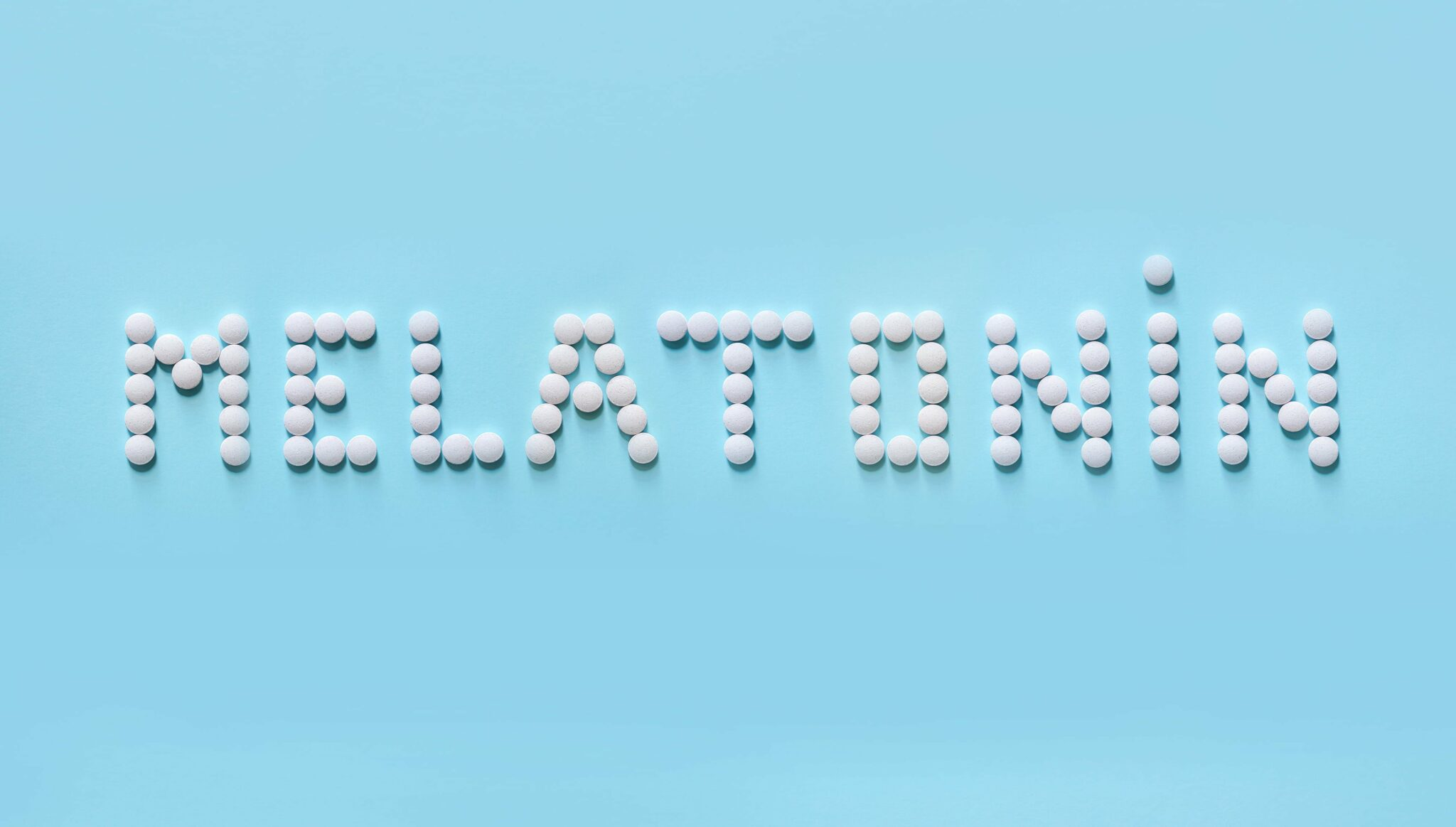 """The word """"melatonin"""" spelled with pills against a light blue background."""