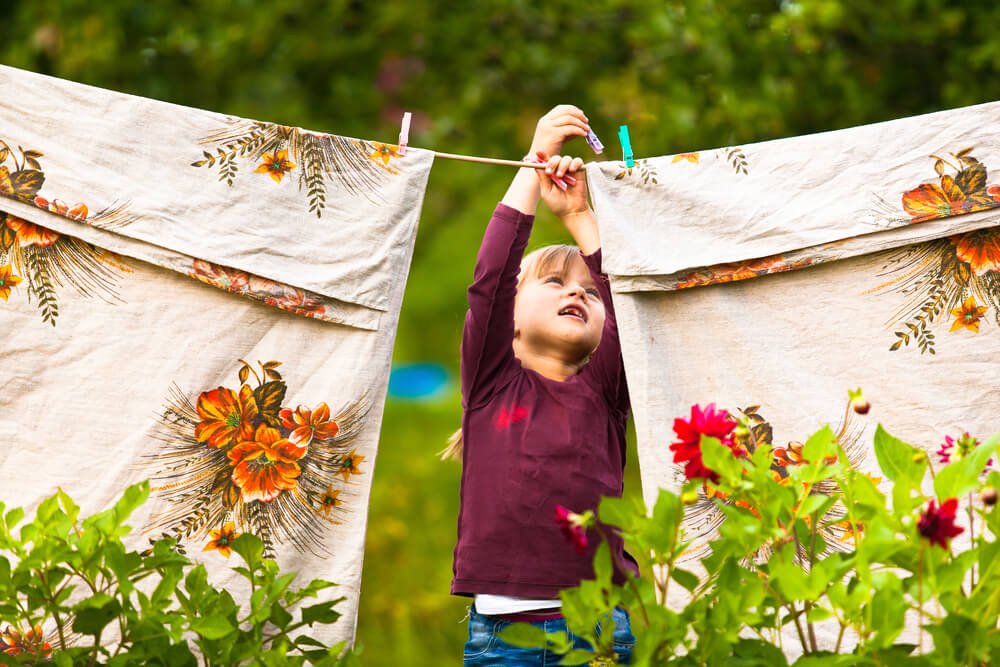 Funny little girl with the clothesline air drying bamboo bed sheets