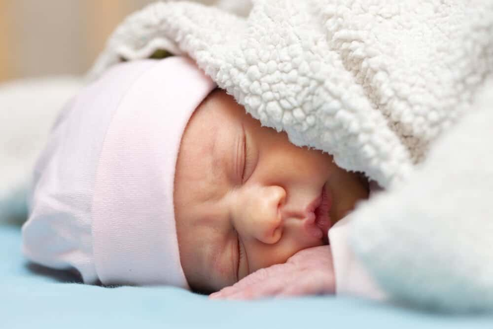 newborn baby sleeps under blanket while sleeping on stomach.
