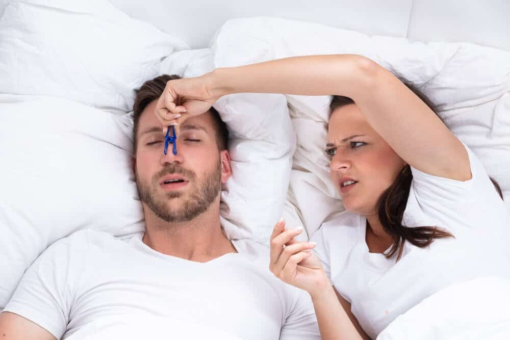 Frustrated Young Woman Trying To Stop Man's Snoring With Clothespin On Bed .