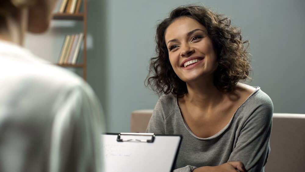 Young happy lady talking with psychologist at clinic, session of depression and sleep therapy