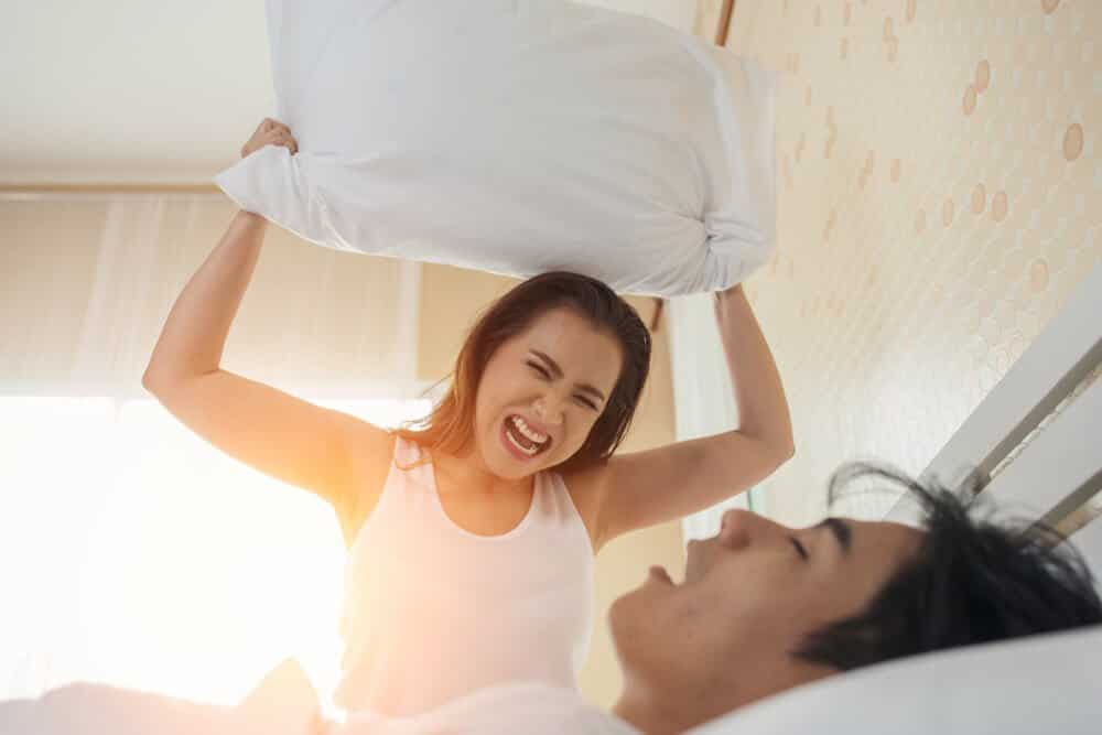 Woman, angry at her boyfriend for snoring, is about to hit him with a pillow.