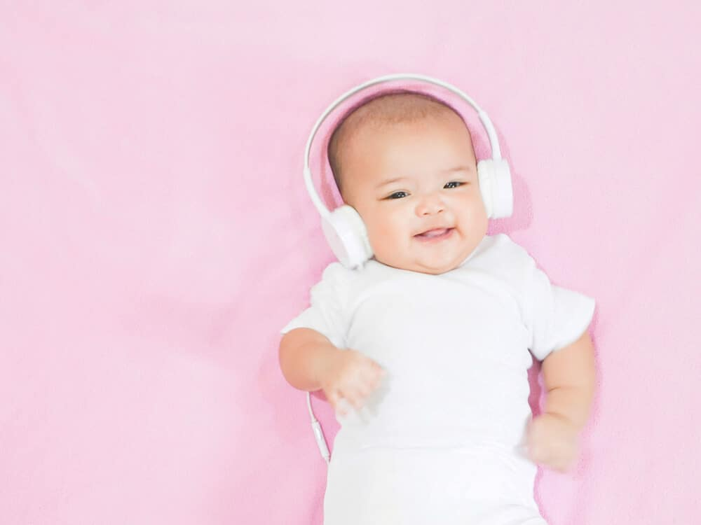 Blur hands of Asian baby girl wear white headphone and white shirt on pink background. Baby waves her hands aling the music from white headphones with sweet smile.; sleep music for babies concept.; lullabies for babies to sleep concept.