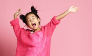 Asian kid girl in pink sweater, white pants and funny buns sings singing dancing on pink background; sleep music for kids concept.