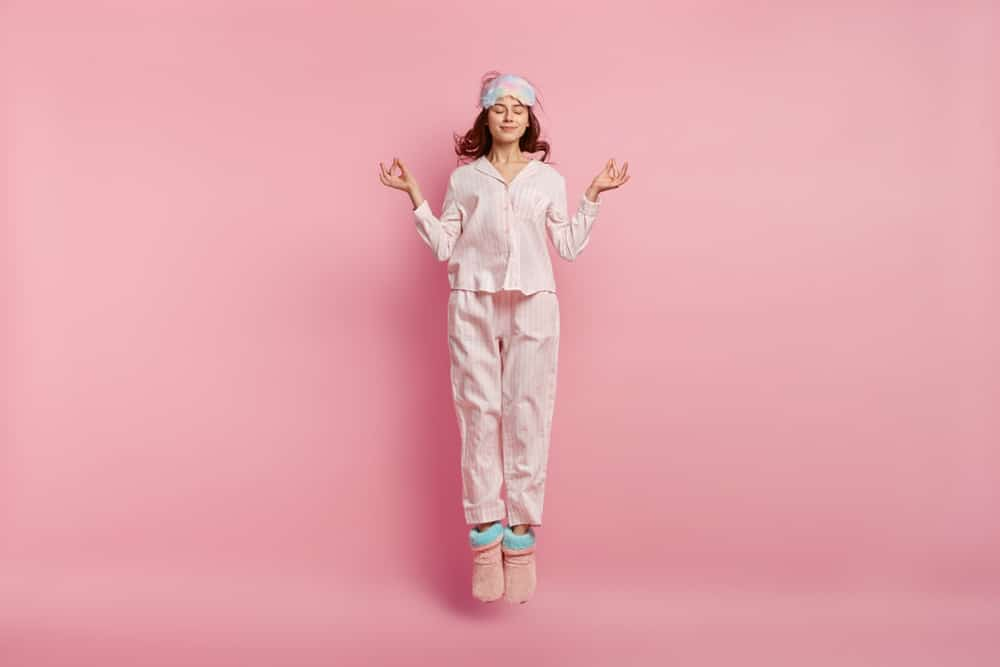 A woman meditating and wearing pink pajamas and standing in front of a pink background.