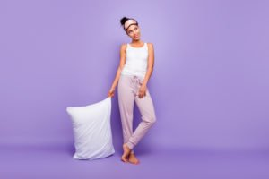 A woman in pajamas standing against a purple wall while holding a memory foam pillow.