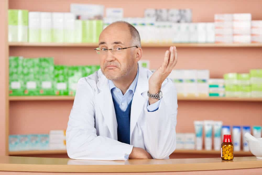 Thoughtful pharmacist standing over the drugstore background; over-the-counter sleep aids versus prescription drugs concept.