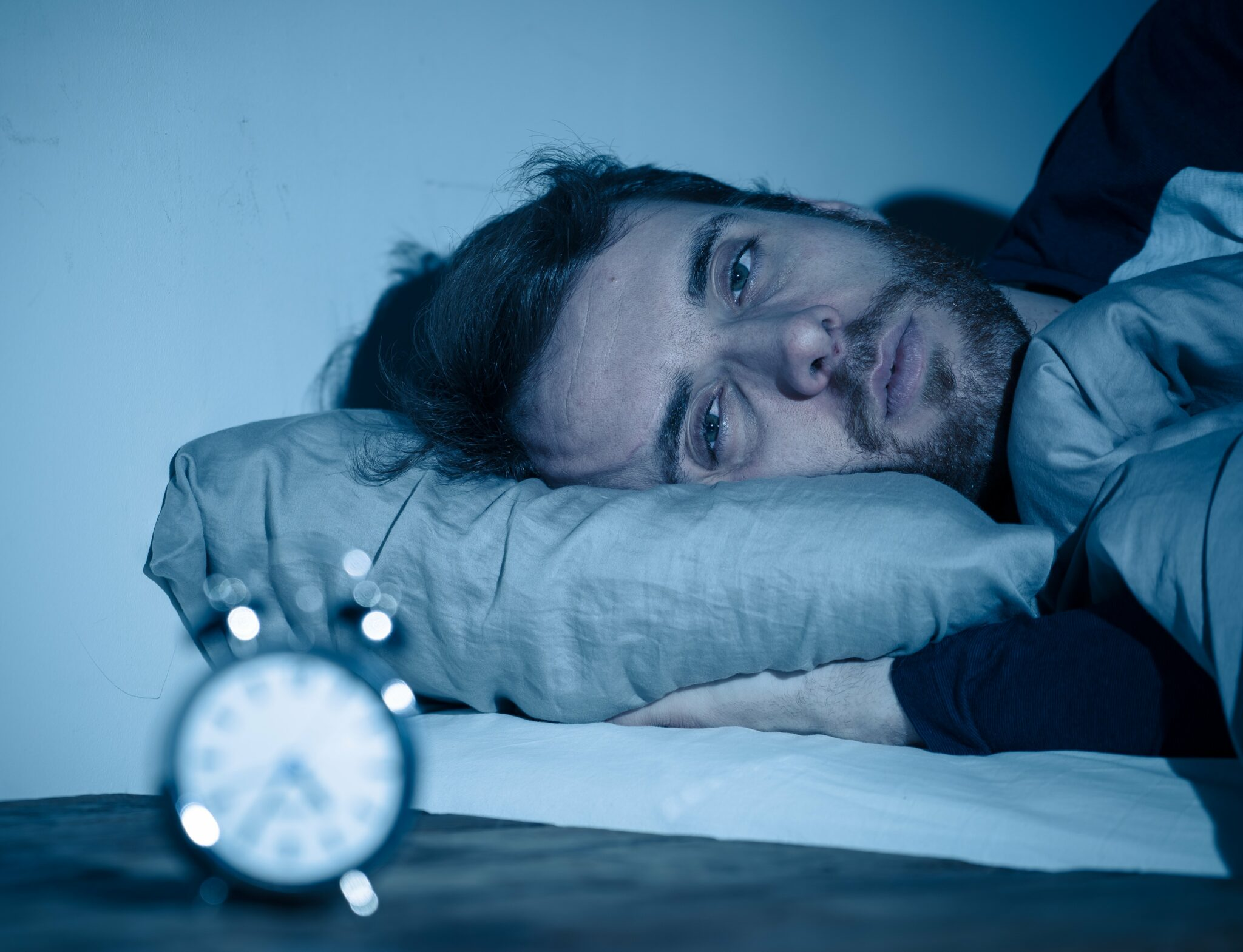 A man with a sleep disorder laying in a bed staring at an alarm clock.