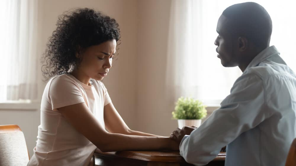 African spouses married couple sit together hold hands loving husband soothing sad wife asks for forgiveness, unfortunate pregnancy miscarriage, difficulties in life relations, health problems concept
