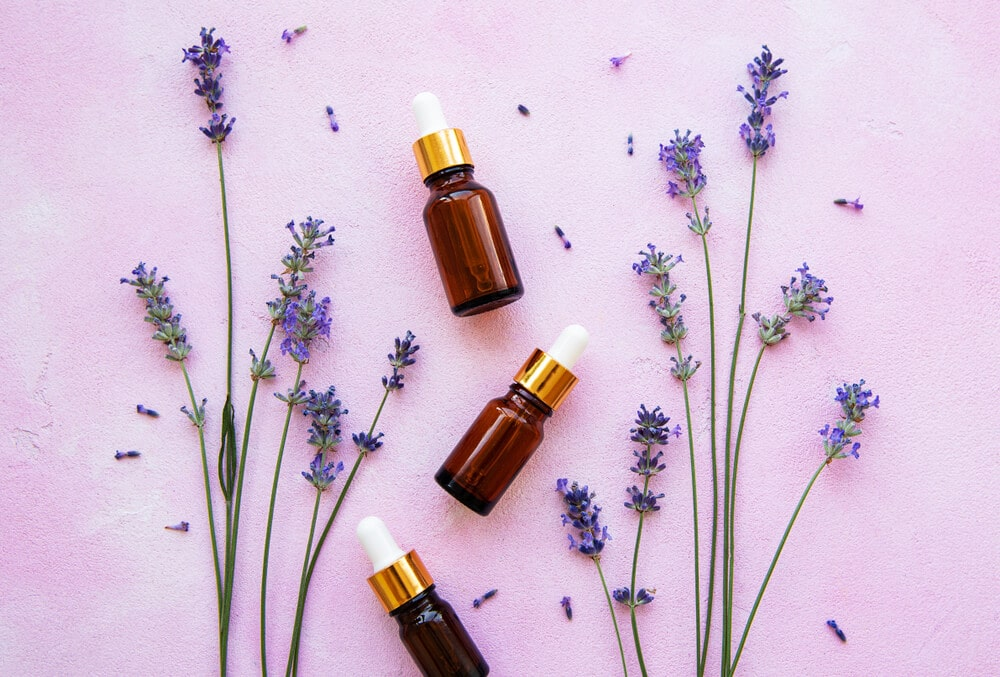 Flat lay composition with lavender flowers and natural cosmetic on pink concrete background