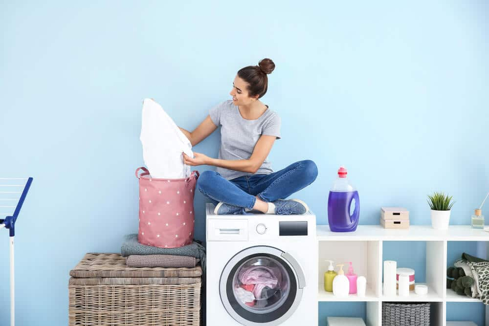 Beautiful young woman with clean laundry sitting on washing machine at home; how to wash bamboo sheets concept.
