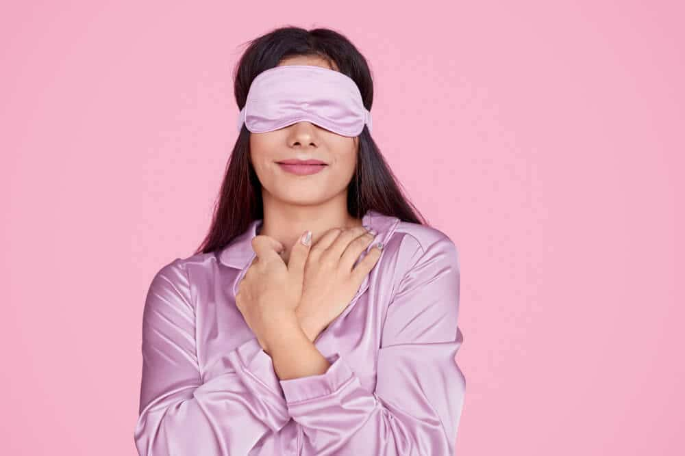 Young lady in sleep mask touching delicate silk sleepwear and enjoying softness and comfort while resting against pink background
