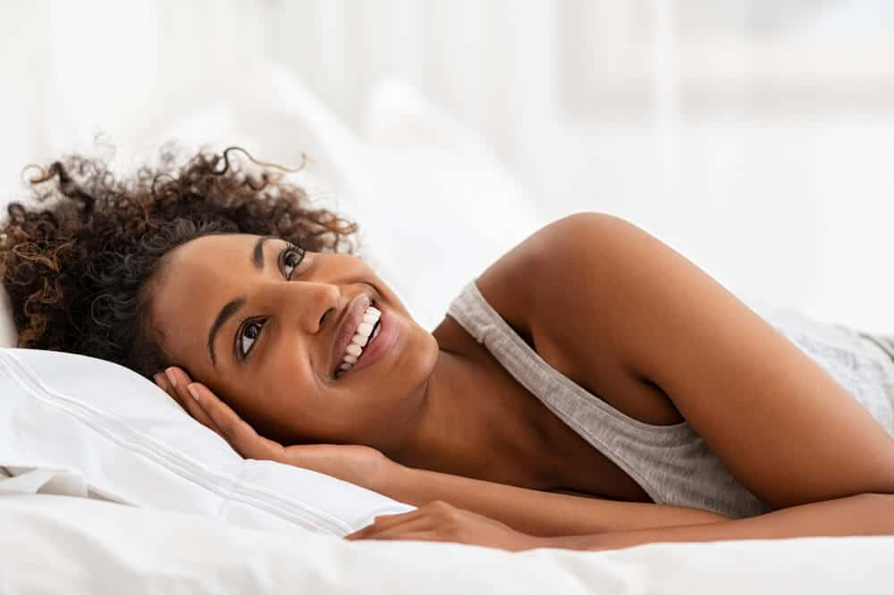 Cheerful young woman laughing while lying on bed. Happy african american girl in bed after sleep feeling refreshed. Relaxed woman with curly hair get up of bed while looking up with copy space.