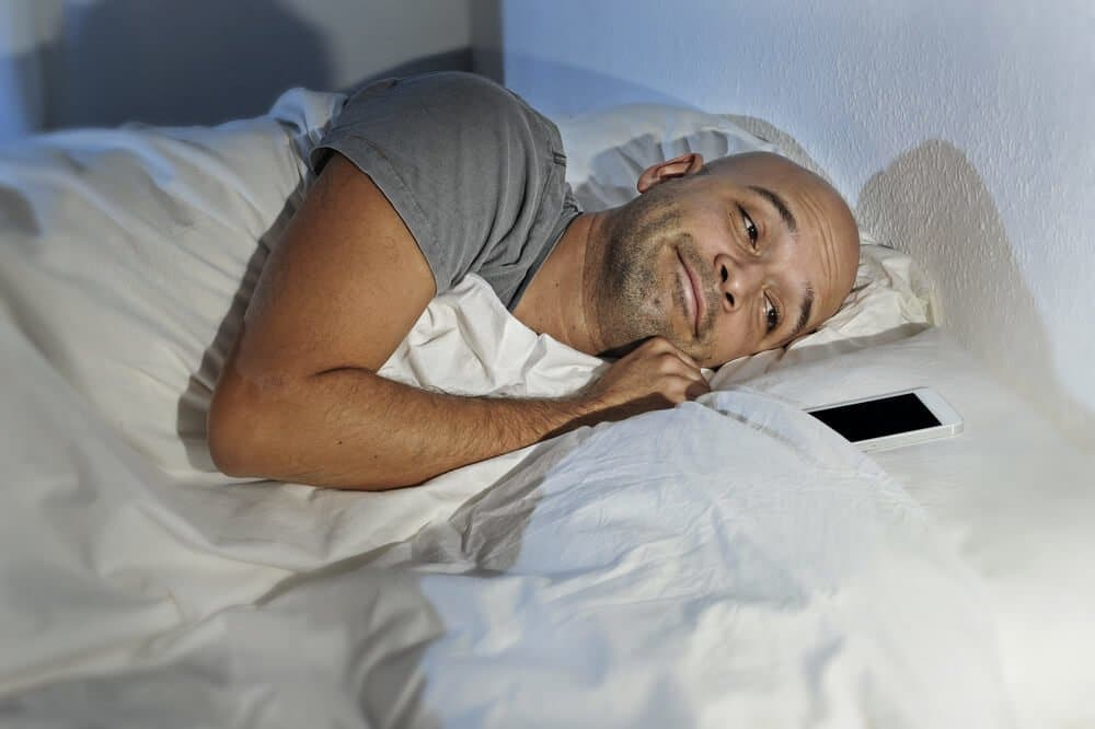 young man cell phone addict in bed at night sleeping happy at home together with mobile phone on internet communication, smartphone and social network addiction concept