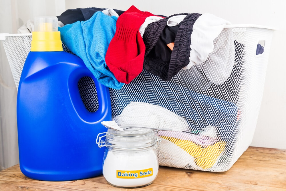 Baking soda with detergent and pile of dirty laundry