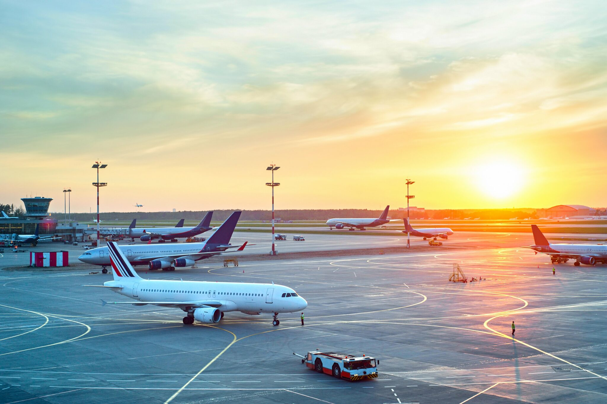 An outdoor airport lot with multiple airplanes at sunset.