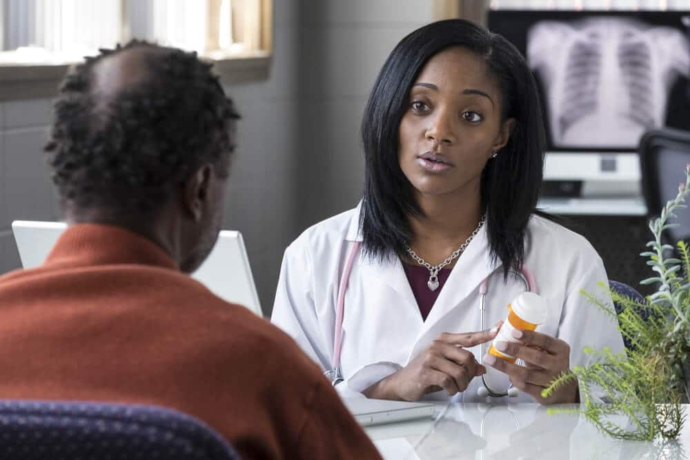 A black female physician prescribing Trazodone for sleep to an older black male patient