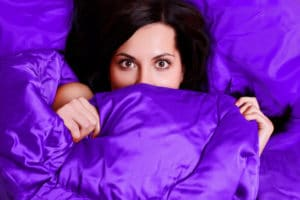 A woman hides her face behind bright purple organic bed sheets.