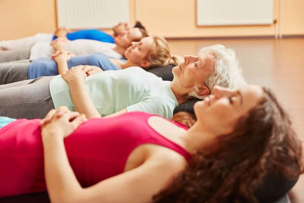 Group of people with senior relaxing making breathing exercise at yoga class.