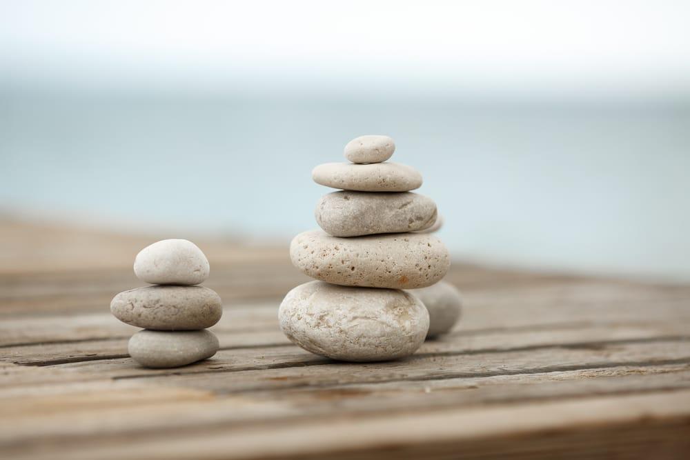 Stacks of meditation stones on a wooden dock.