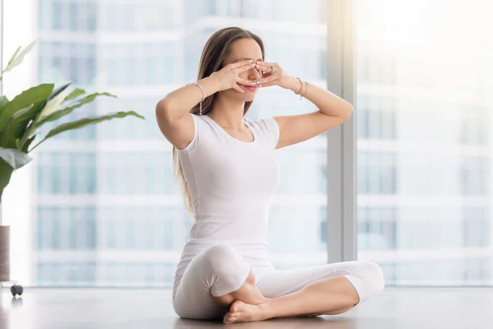 Young woman practicing yoga, sitting in Sukhasana pose, performing Humming Bee Breathing exercise, Bhramari Pranayama technique, working out, wearing sportswear, white t-shirt, pants, full length