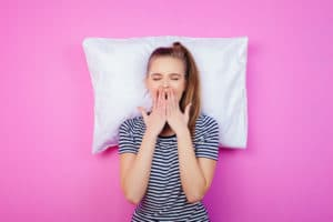 the young woman with a pillow on the pink wall; Dodow review concept.