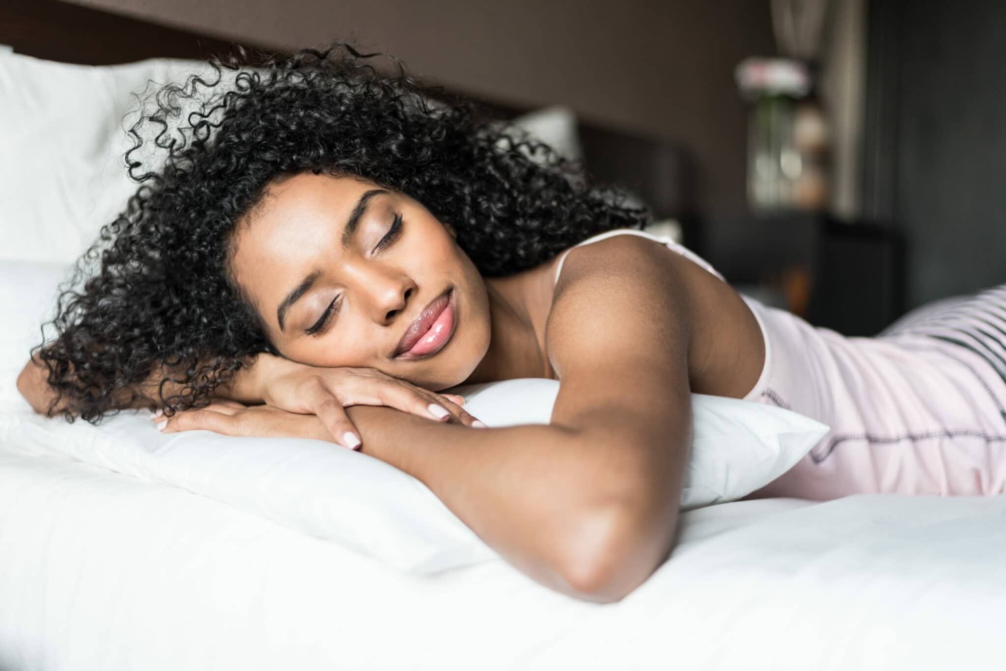A woman sleeping in bed with curly hair.