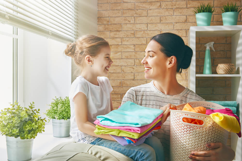 Beautiful young woman and child girl little helper are having fun and smiling while doing laundry at home; how to soften sheets concept.