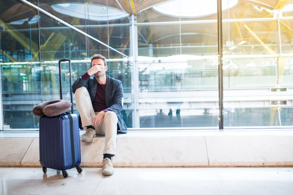 A man with jet lag who is sitting at an airport with his luggage and his head on his hand.