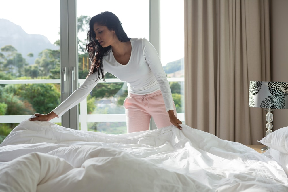 A woman making her bed with fitted sheets and a comforter in front of a window.