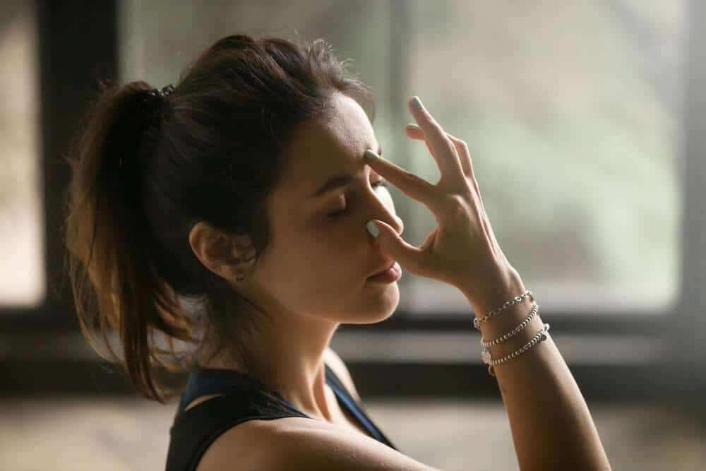 Young attractive woman practicing yoga at home, making Alternate Nostril Breathing exercise, nadi shodhana pranayama pose, working out wearing wrist bracelets, indoor close up image, studio background