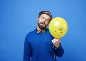 Man sleeping in standing position holding yellow balloon against a blue background.