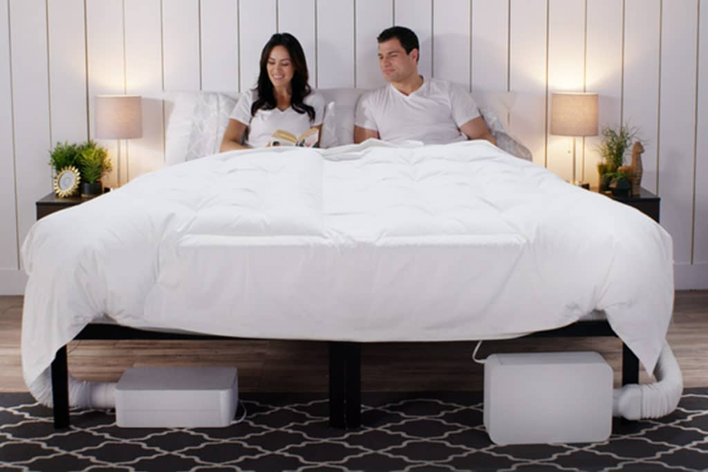 A man and woman on a white bed with two BedJets.