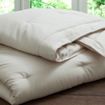 A folded handmade comforter from PlushBeds rests on a wooden surface.