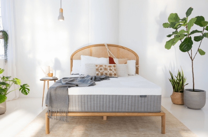 A Brentwood Home Cypress mattress rests on a bed frame in a neutral color room.