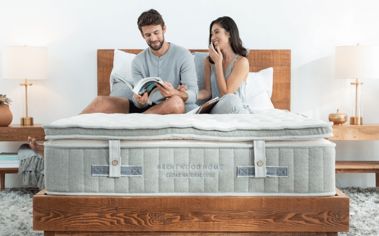 A man and woman relax on a Brentwood Home Cedar Natural Luxe mattress.