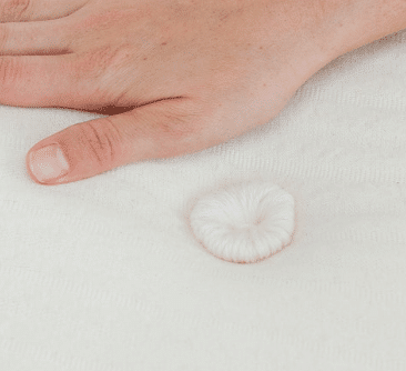 a hand lays on a mattress with wool tufting.
