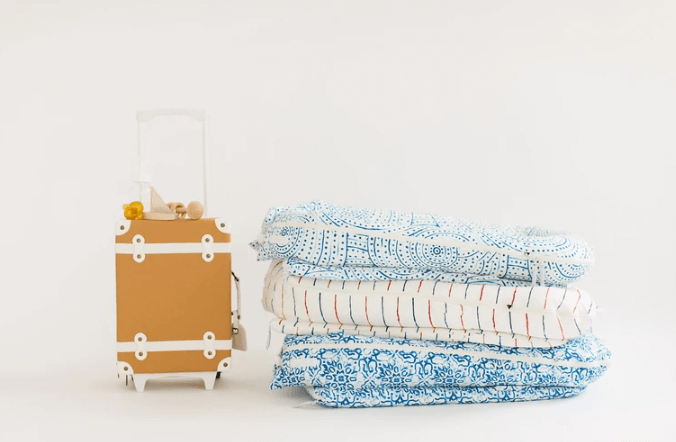 Dock-A-Tots are easy to transport. Suitcase next to stack of baby loungers.